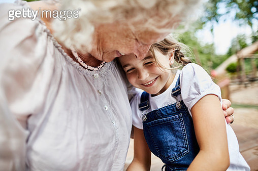 Happy grandmother embracing granddaughter outdoors - gettyimageskorea