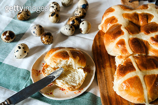 Easter homemade hot cross buns, buttered with butter, quail unpainted eggs - gettyimageskorea