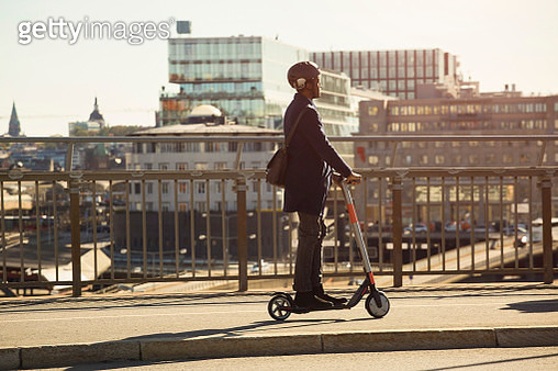 Full length of young man riding electric push scooter on bridge in city - gettyimageskorea