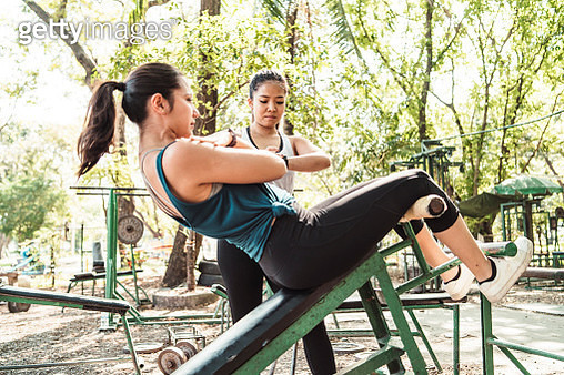 Young woman doing sit-ups outdoor with her personal trainer - gettyimageskorea