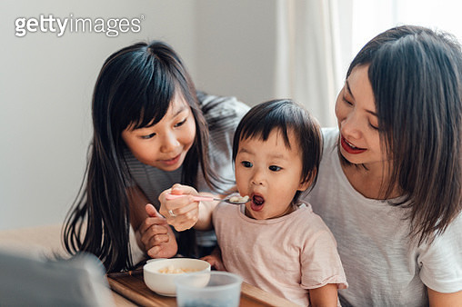 Young Girl Helping Her Mother Feeding Food To Toddler Sister - gettyimageskorea