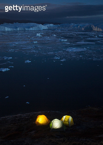 Camping tents at night on shore of Ilulissat Icefjord, Greenland, Denmark - gettyimageskorea