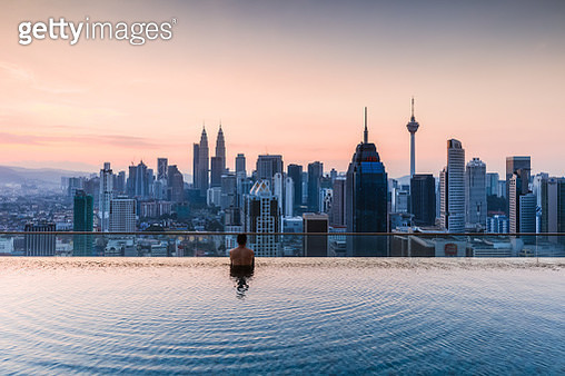 Man in a infinity pool with Kuala Lumpur skyline, Malaysia (MODEL and PROPERTY RELEASED) - gettyimageskorea