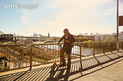 Full length of young man standing with electric push scooter by railing on bridge in city - gettyimageskorea