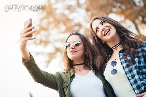Two beautiful young women taking selfie in autumn day - gettyimageskorea