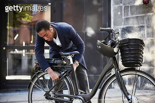 Young male commuter locking electric bicycle against building in city - gettyimageskorea