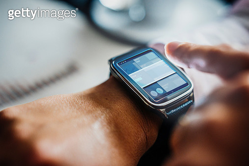 Businesswoman using smart watch to check stock exchange prices. - gettyimageskorea