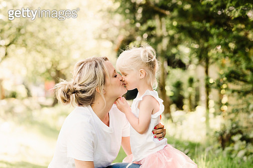 Happy mother kissing her little daughter outdoors - gettyimageskorea
