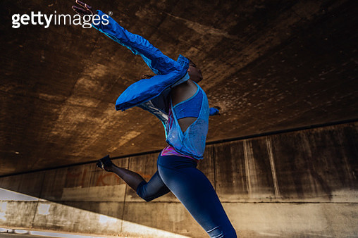 Woman jumping on sidewalk under bridge - gettyimageskorea