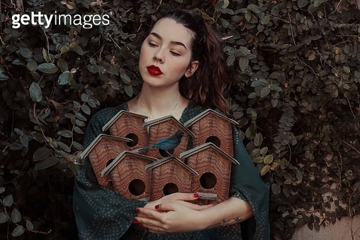 Young Woman Standing With Bird On Birdhouse Against Ivy - gettyimageskorea