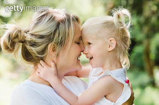 Happy mother cuddling her daughter in nature - gettyimageskorea