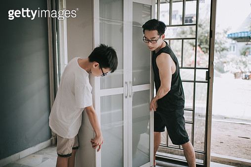 an asian chinese family moving house father and son moving cabinet - gettyimageskorea