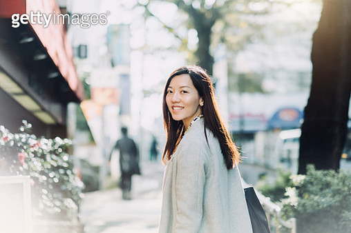 Beautiful Asian woman looking back with smile on the street - gettyimageskorea