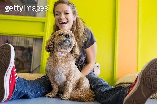 Laughing woman with dog - gettyimageskorea