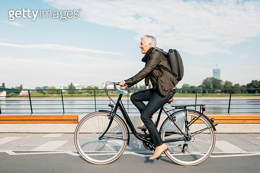 Mature Woman Riding Bicycle. - gettyimageskorea