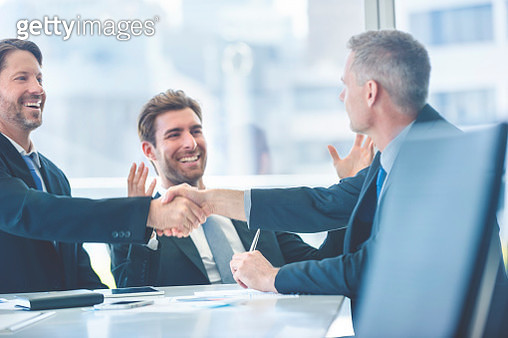 Businessmen shaking hands at the board room table. - gettyimageskorea