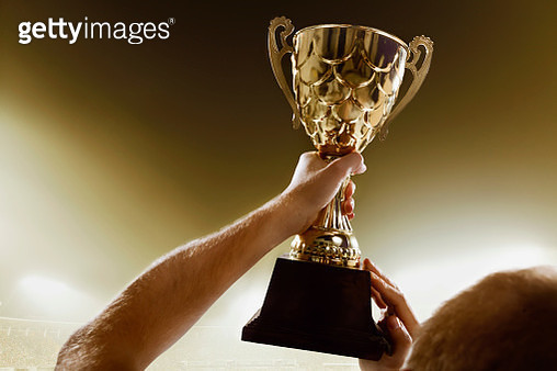 Athlete holding trophy cup above head in stadium - gettyimageskorea