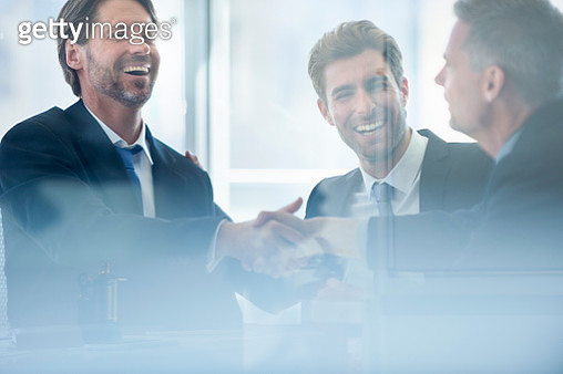 Businessmen shaking hands at the board room table - gettyimageskorea