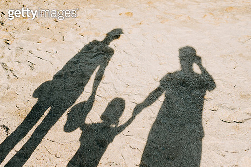 Shadow on sandy beach of a loving family of three holding hands relaxing on a lovely sunny day - gettyimageskorea
