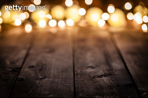 Empty rustic wooden table with blurred Christmas lights at background - gettyimageskorea
