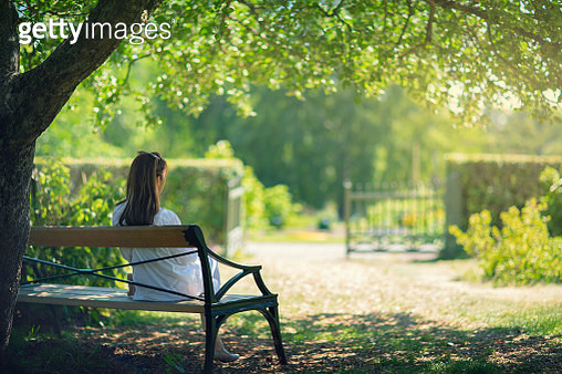 A woman sitting down on a bench in a garden in the shade of a tree and enjoying the surroundings. - gettyimageskorea