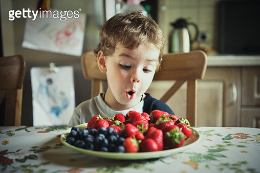 Cute Boy Looking At Fruits In Plate At Table - gettyimageskorea