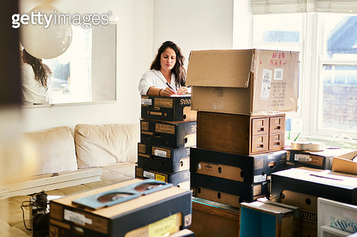 Woman labelling boxes in the process of packing to move house - gettyimageskorea