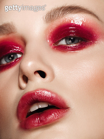 Beautiful woman with glossy red eyeshadow and lipstick - gettyimageskorea