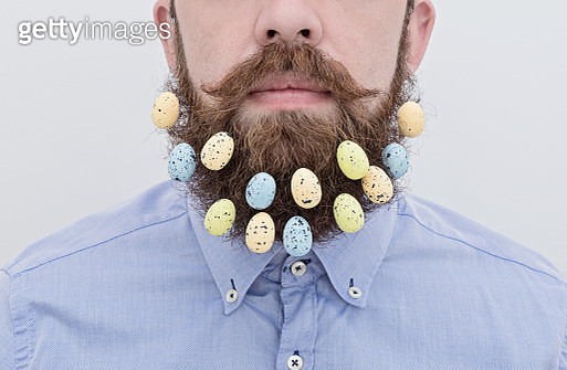 Bearded Man With Eatser Eggs Against White Background - gettyimageskorea