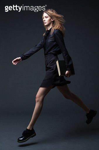 Young attractive fashion girl with big book back to school. Studio shot. - gettyimageskorea