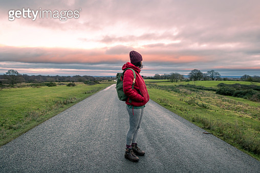 A woman hiking along a road looks back at an atmospheric pink sky - gettyimageskorea