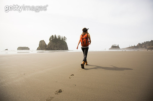 A woman hiking along a remote beach. - gettyimageskorea