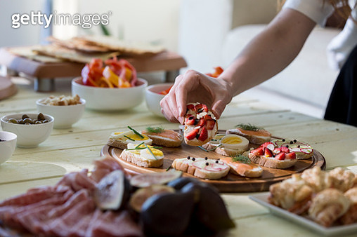 Hand reaching for appetizers on table - gettyimageskorea