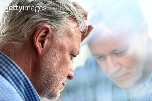 Serious concerned caucasian senior man posing looking down - gettyimageskorea