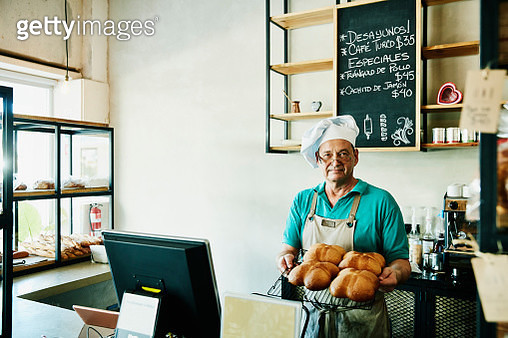 Baker standing behind counter in shop holding tray of freshly baked bread - gettyimageskorea