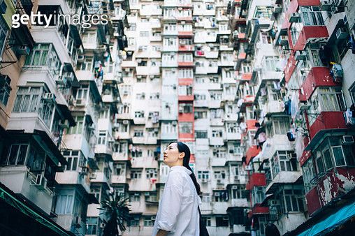 Low angle view of woman surrounded by old traditional residential buildings and looking up to sky in city - gettyimageskorea