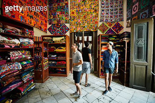 Three friends shopping for blankets in local market while on vacation - gettyimageskorea