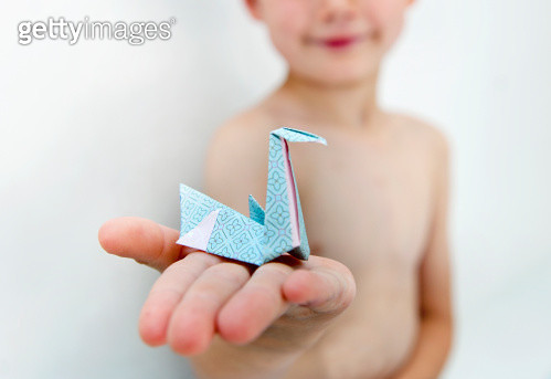 A little boy holding an origami swan - gettyimageskorea