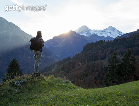 Male hiker pauses on mountain crest, sunrise - gettyimageskorea