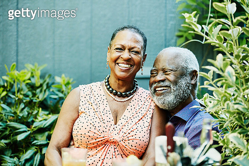 Smiling senior woman sitting in husbands lap at outdoor cafe on summer afternoon - gettyimageskorea