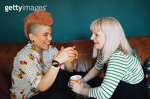Close up of female couple laughing on sofa - gettyimageskorea