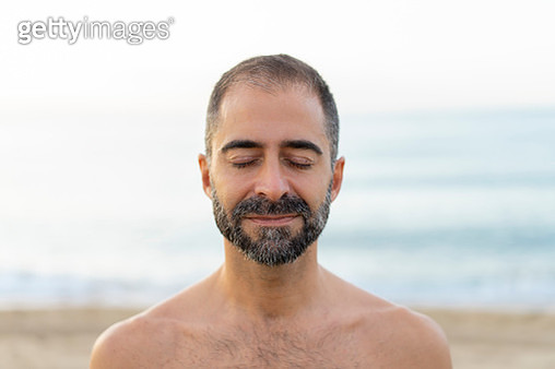 Portrait of happy man on a beach in the evening - gettyimageskorea