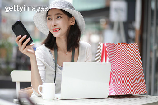 Young woman with smartphone at sidewalk cafe - gettyimageskorea