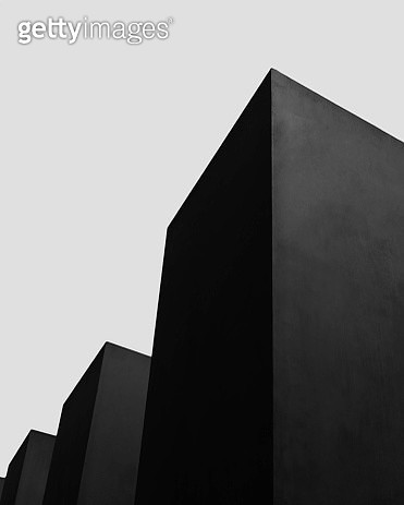 Black architectural boxes and towers standing tall on grey background - gettyimageskorea