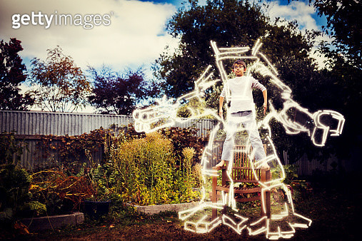 Boy stands on chair in garden and imagines himself inside a futuristic exoskeleton - gettyimageskorea
