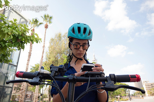 Medium Shot of Young Woman Using Smartphone while Sitting on Electric Bike - gettyimageskorea