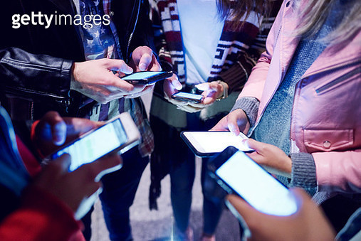 Mid section of young adult friends standing in circle looking at smartphones - gettyimageskorea