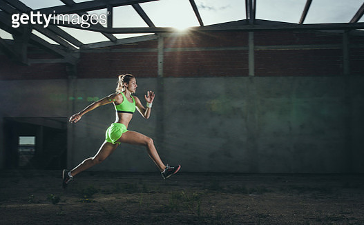 Side view of determined athletic woman jumping while running. Copy space. - gettyimageskorea