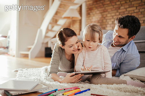 Close up of a happy young family surfing the net on digital tablet - gettyimageskorea