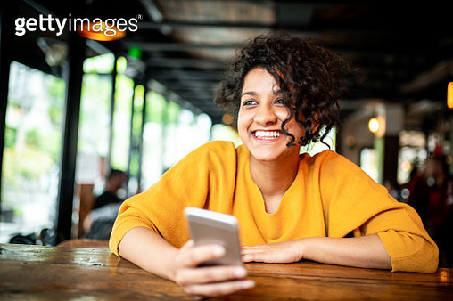 Beautiful smiling Indian woman using mobile phone at the coffee shop - gettyimageskorea